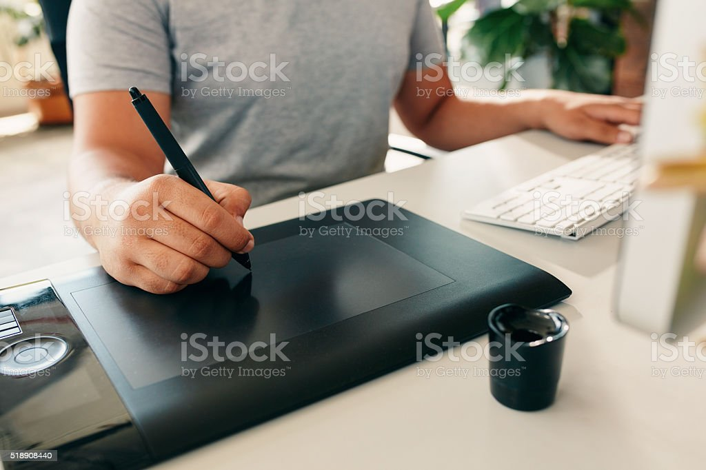 Graphic designer using digital tablet and computer in the office stock photo