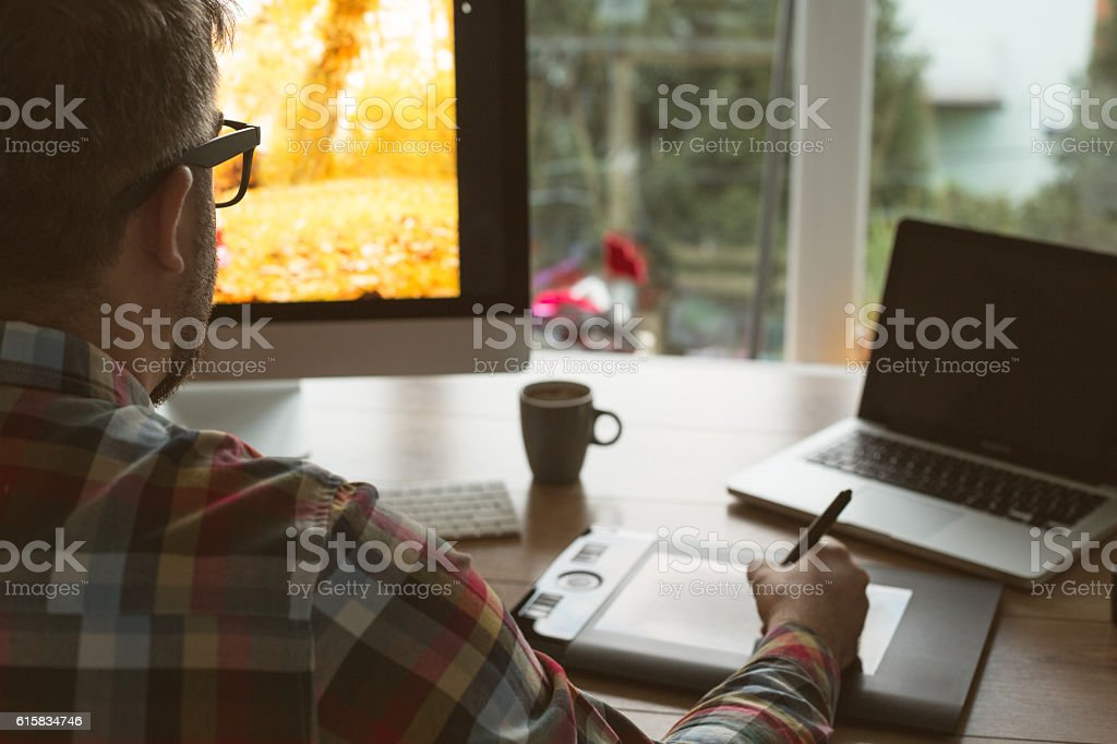 Graphic designer using digital tablet and computer stock photo