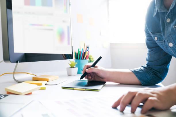 diseñador gráfico usando tableta gráfica para trabajar en el escritorio - oficina de empleo fotografías e imágenes de stock