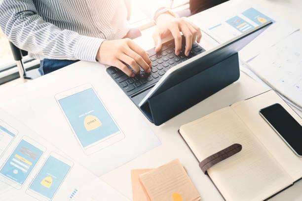 Ux Diseñador gráfico utilizando el proceso de aplicación de planificación creativa de tabletas y el desarrollo prototipo de estructura alámbrica para teléfono inteligente web o móvil. - foto de stock