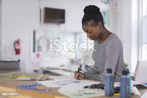 A graphic designer sketches out prototypes for an idea onto paper. She is using a pen and leaning over her desk to concentrate. There are various pens, papers, and art supplies setting on the desk. Light is coming in from large exterior windows in the background.