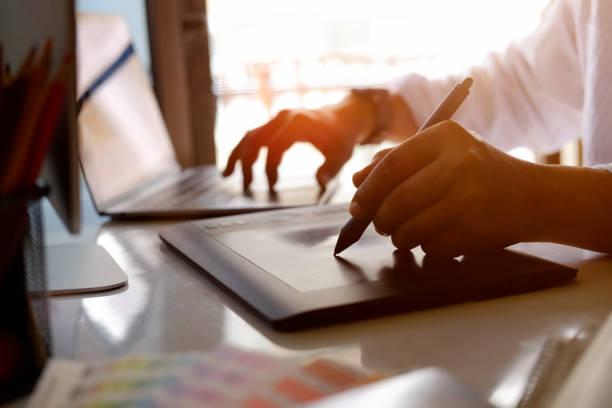 Graphic designer working in studio. Attractive designer working with digital tablet and tablet at design studio office. illustrator stock pictures, royalty-free photos & images
