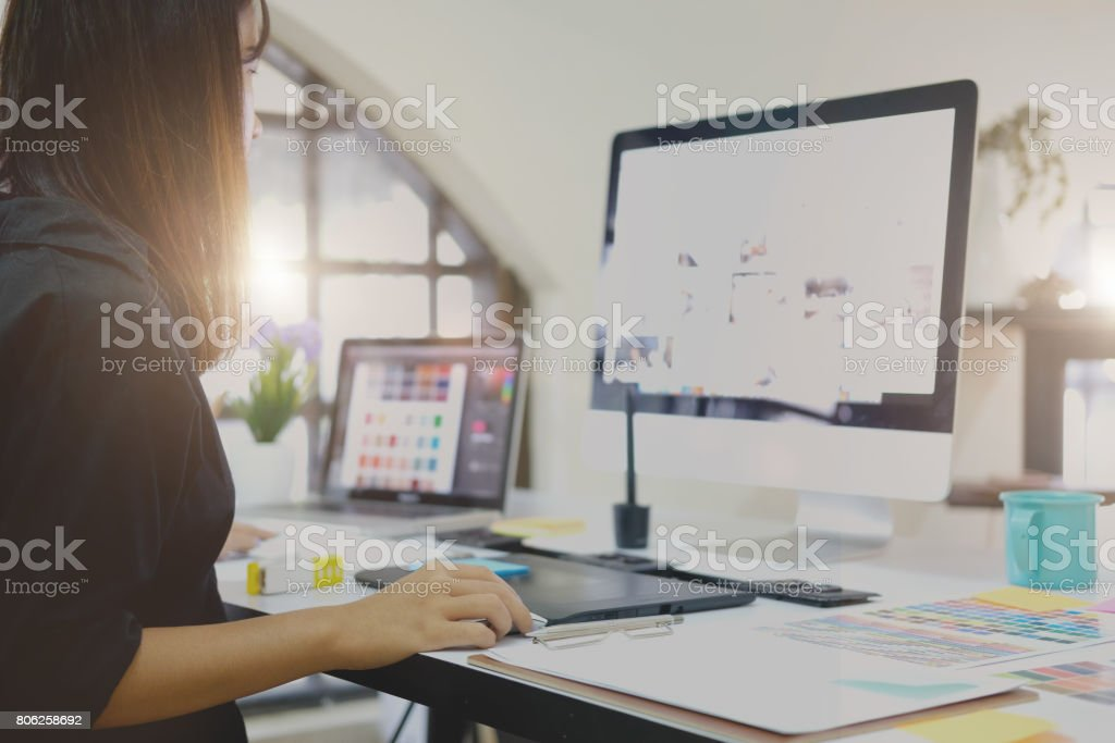 Graphic designer working on computer using digital tablet at office. stock photo