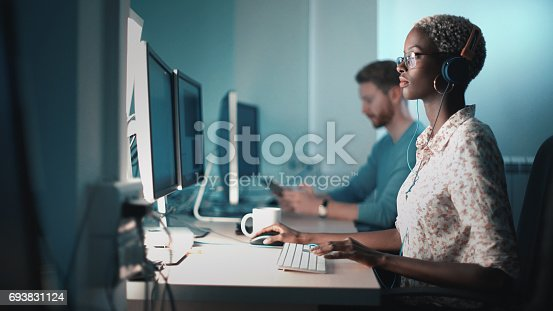 Closeup side view of mid 20's blond black woman doing her design project on a computer. She might be a software developer as well.  She's sitting in front of a desktop computer and sipping a coffee while working on a computer.