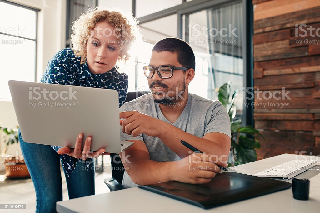 Graphic designers cooperating in design studio stock photo
