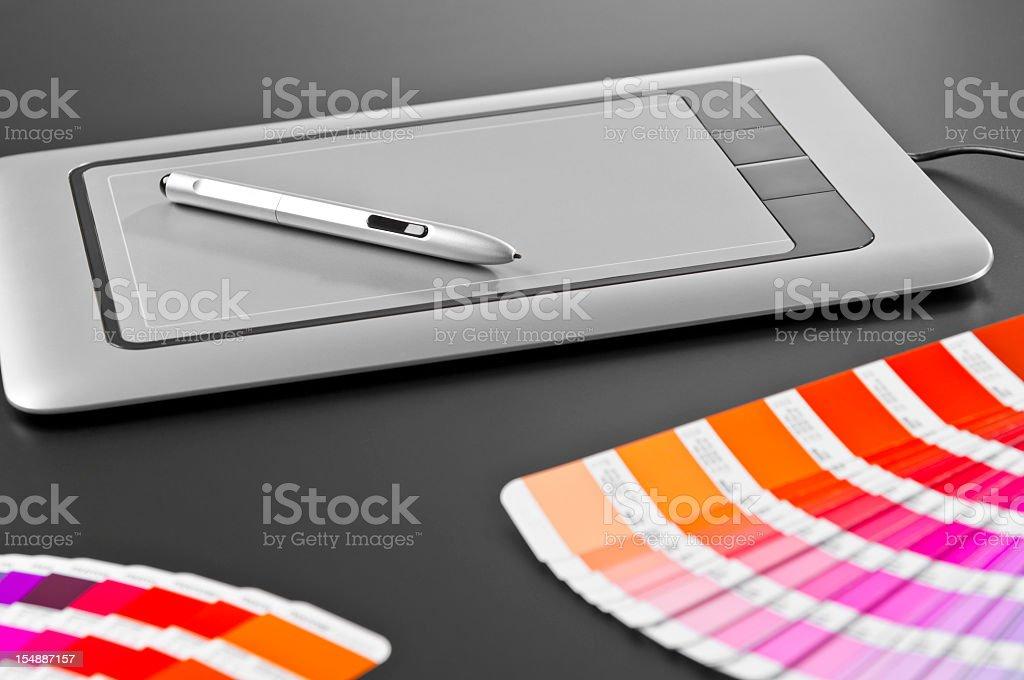 Graphic designer's tools: digital tablet, pen, swatches, dark gray background stock photo