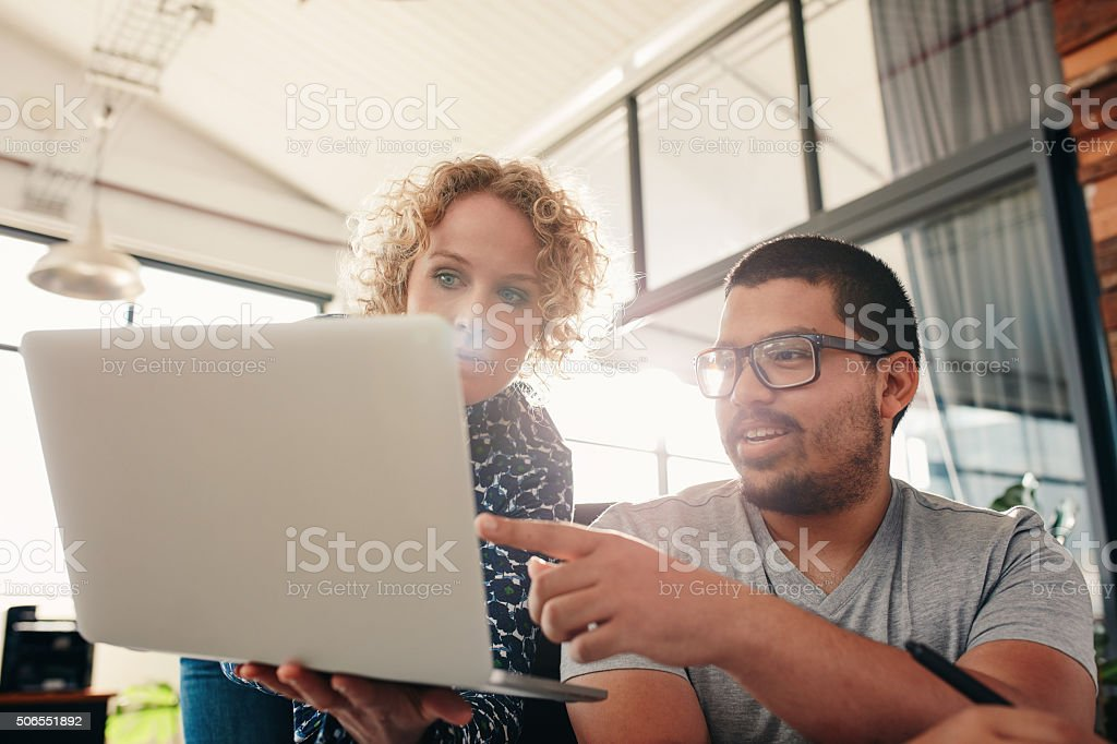 Graphic designers working in office using laptop stock photo