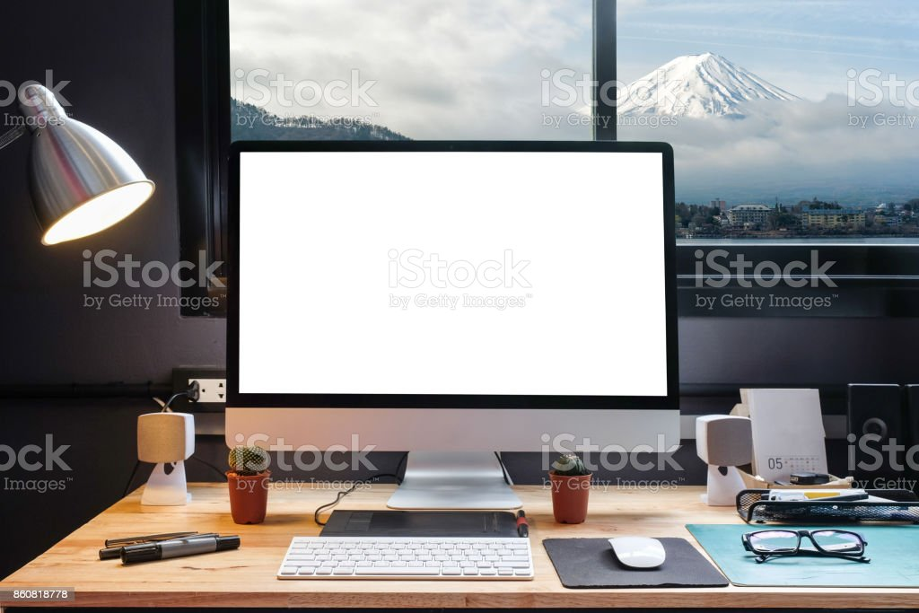 Graphic designer's workspace equipped with a pen tablet, a computer and white screen for text with beautiful Snow Mountain Fuji in Japan from the window stock photo