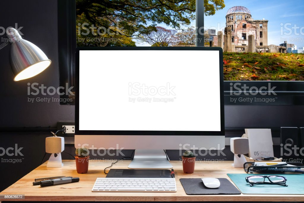 Graphic designer's workspace equipped with a pen tablet, a computer and white screen for text with Hiroshima Atom Bomb Dome from the window stock photo