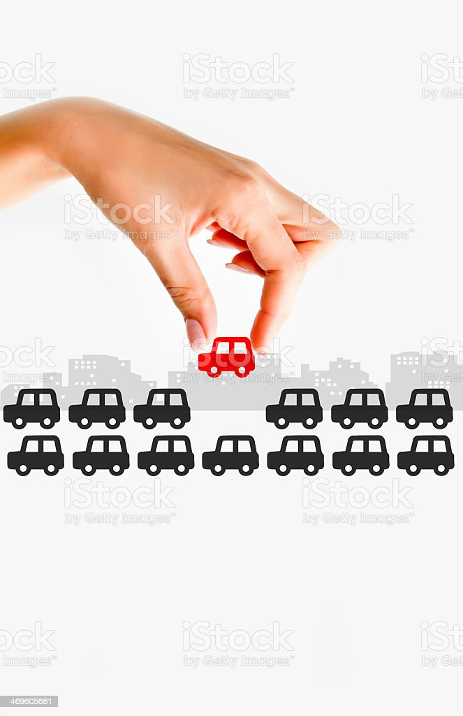 Graphic of hand placing red car in busy street of black cars stock photo