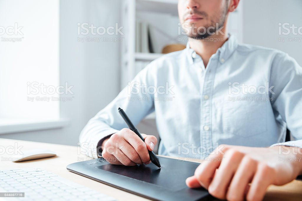 Graphic tablet used by serious young man designer in office stock photo