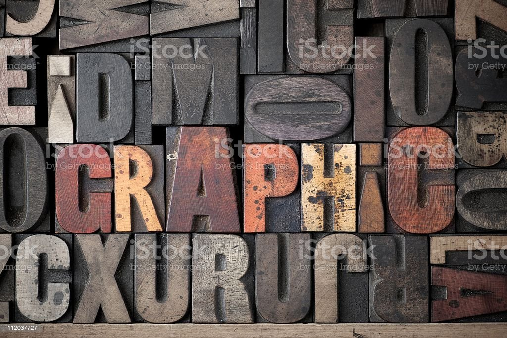 Graphic wooden letters stamps set lettering stock alphabet The word 'Graphic' spelled out in very old letterpress blocks. Color Image Stock Photo