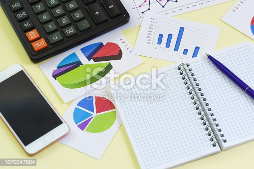istock Graphics, notebook, pen, calculator and phone lie on a yellow background 1070247504