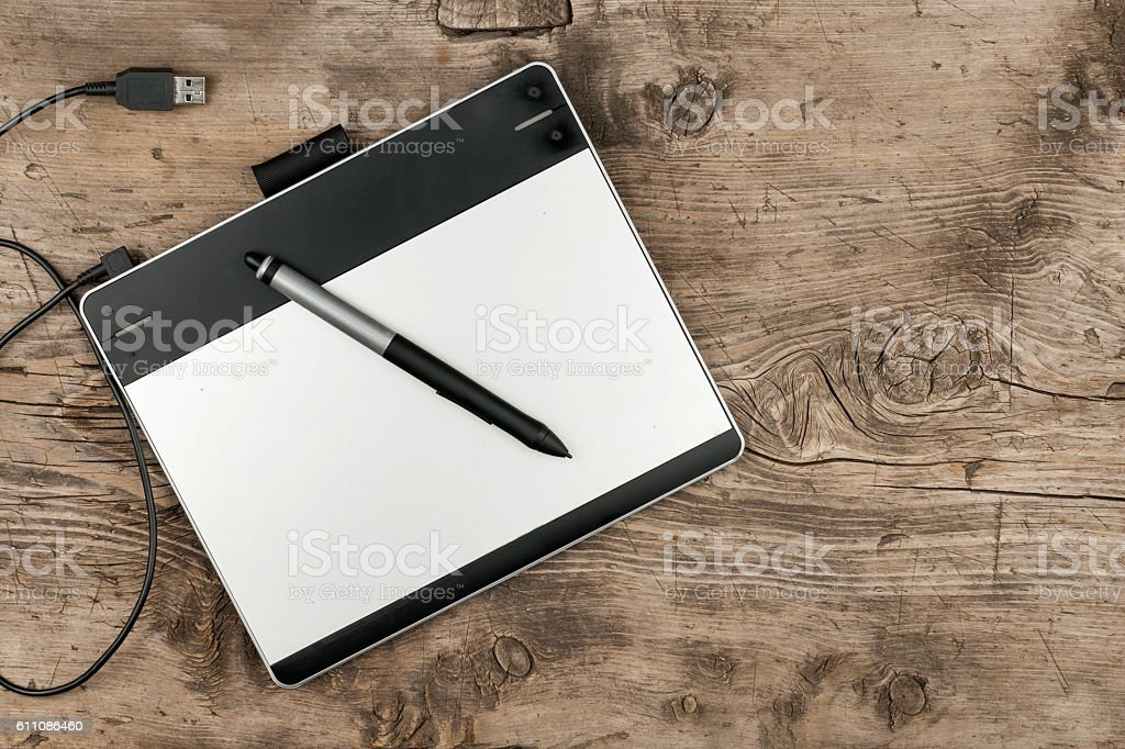 Graphics tablet with stylus lying on a wooden surface stock photo