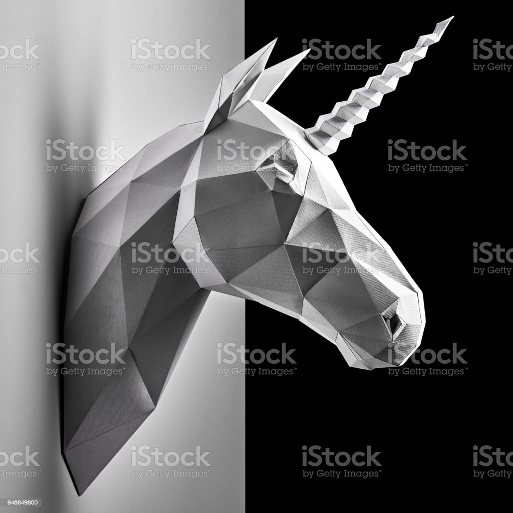Graphitic grey unicorn's head hanging on the contrast white and black wall. stock photo