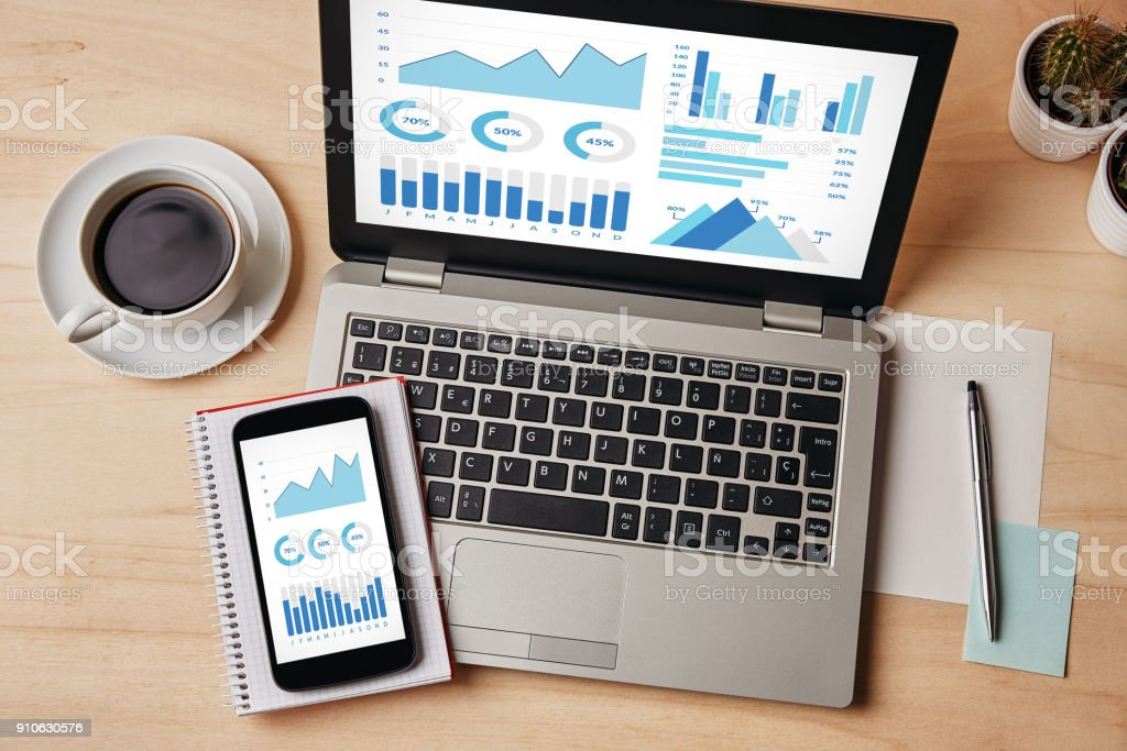 Graphs and charts elements on laptop and smartphone screen stock photo