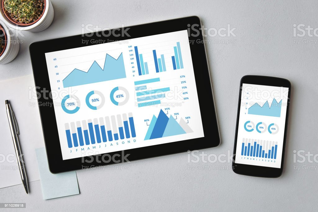Graphs and charts elements on tablet and smartphone screen Graphs and charts elements on tablet and smartphone screen over gray table. All screen content is designed by me. Flat lay Analyzing Stock Photo