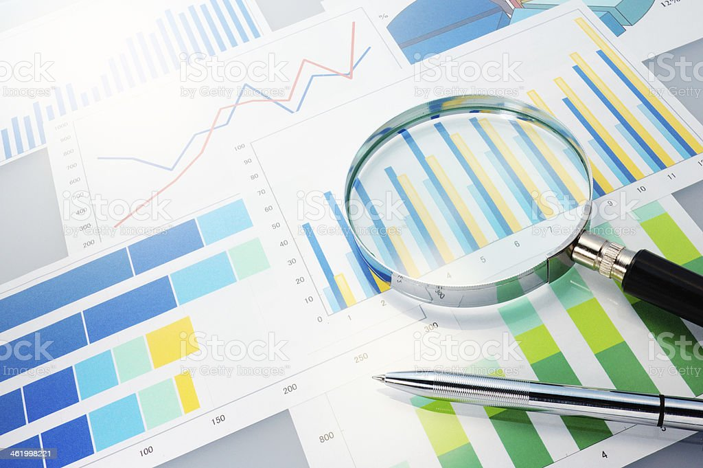 Graphs, magnifier and pen. stock photo