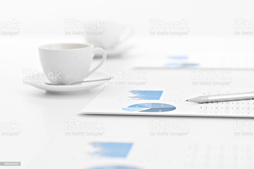 Graphs on paper with cups during a business meeting royalty-free stock photo
