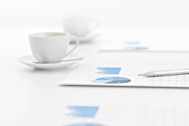 Graphs on paper with cups during a business meeting stock photo