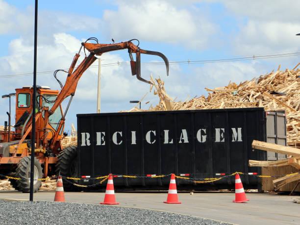 Die Grapeln laden Paletten in Container, um in das Recyclingzentrum transportiert zu werden – Foto