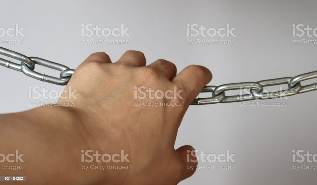 Grasping hands for a silver metal chain stock photo