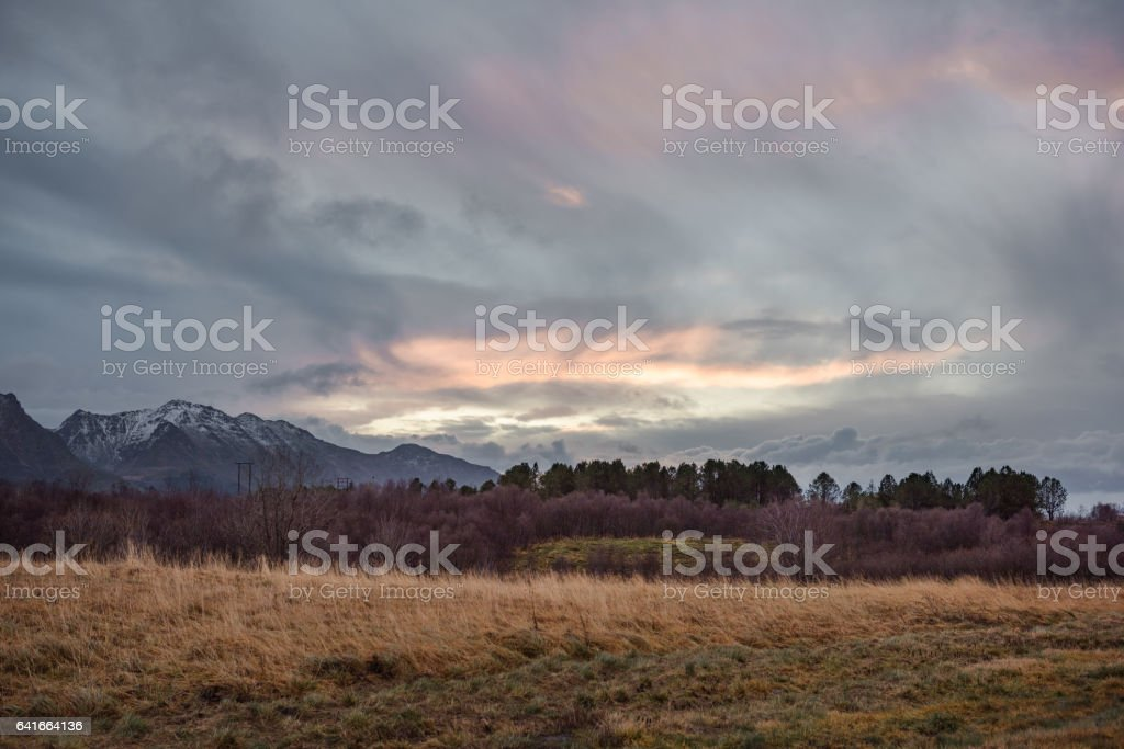 Grass field with trees and mountains on background with colorful cloudscape stock photo