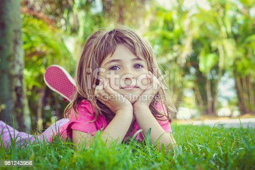 Super cute kid in a colorful outfit lays on the grass with her head in her She looks concerned, unsure, unhappy, neutral. The grass is nice and green and it is a summery day