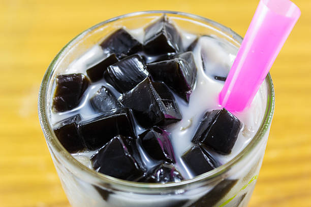 grass jelly in glass grass jelly with milk and ice in glass jello stock pictures, royalty-free photos & images