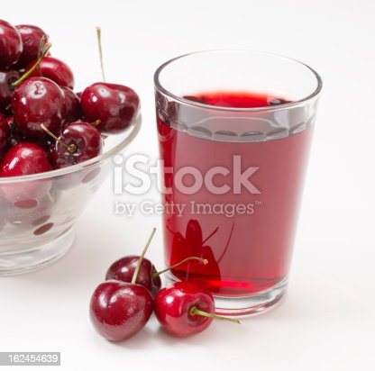 Glass of cherry juice and whole cherries