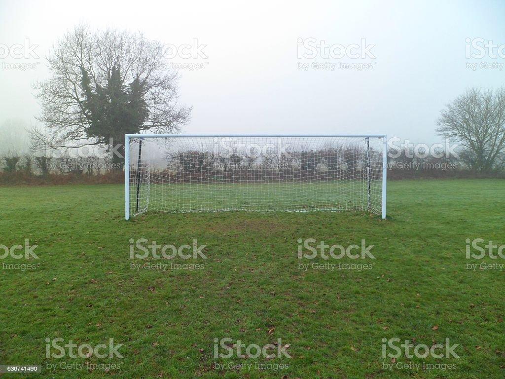 Grass roots amateur football goalposts, crossbar and net on a misty...