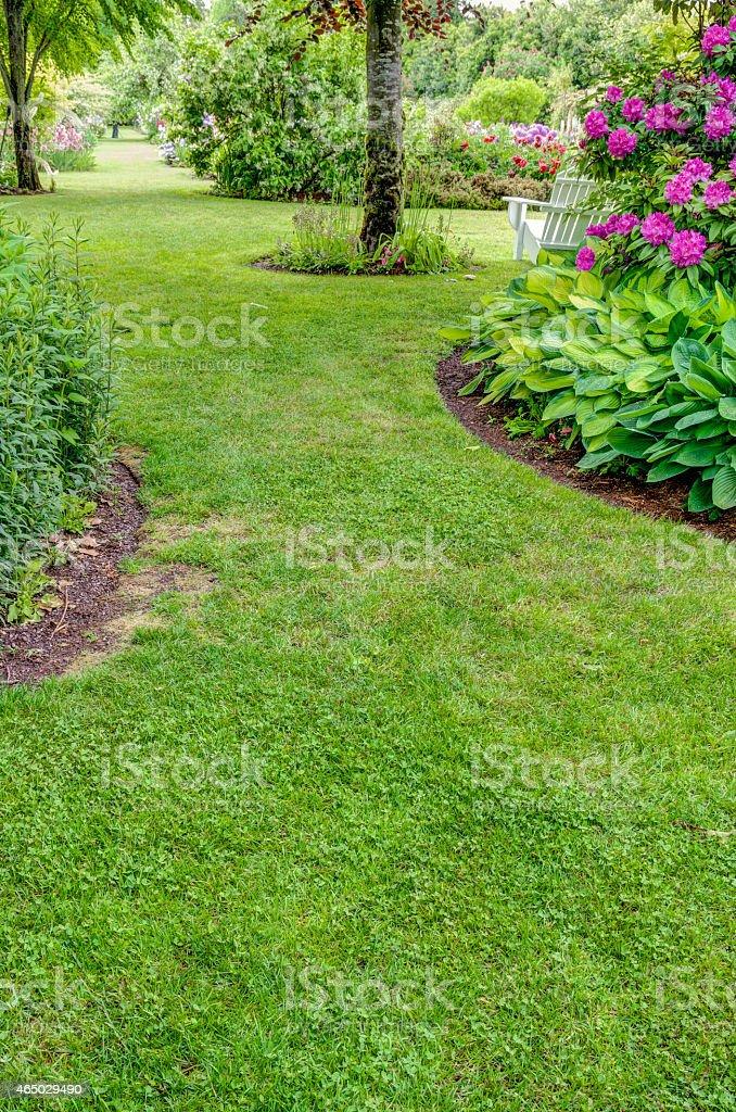 Grass walkway through a garden stock photo