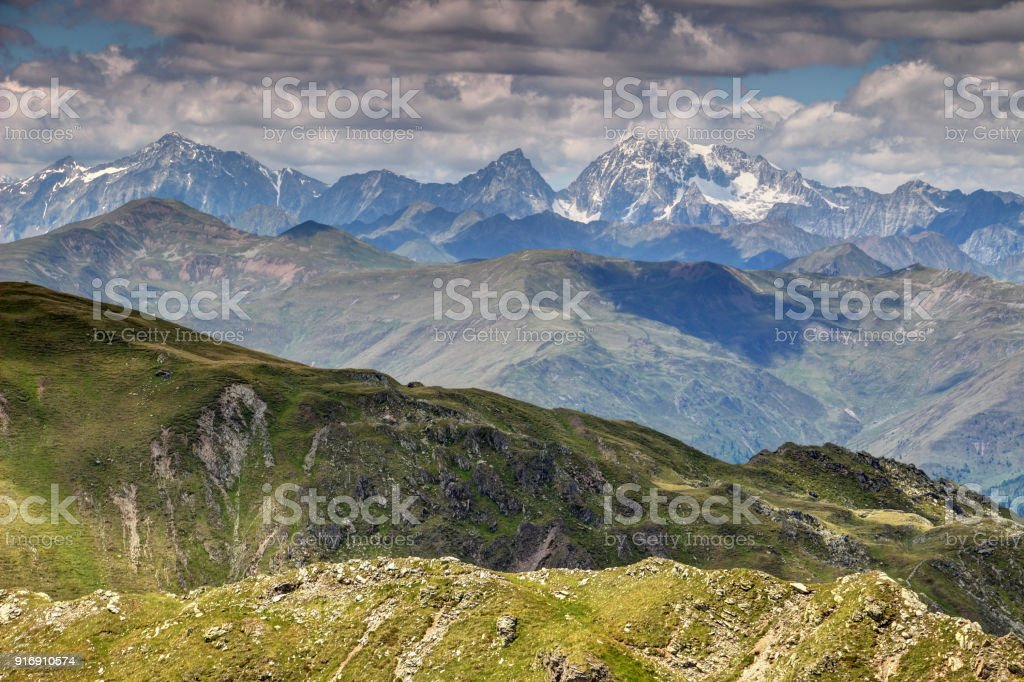Grassy Carnic Alps and jagged Tauern with snowy Hochgall peak stock photo