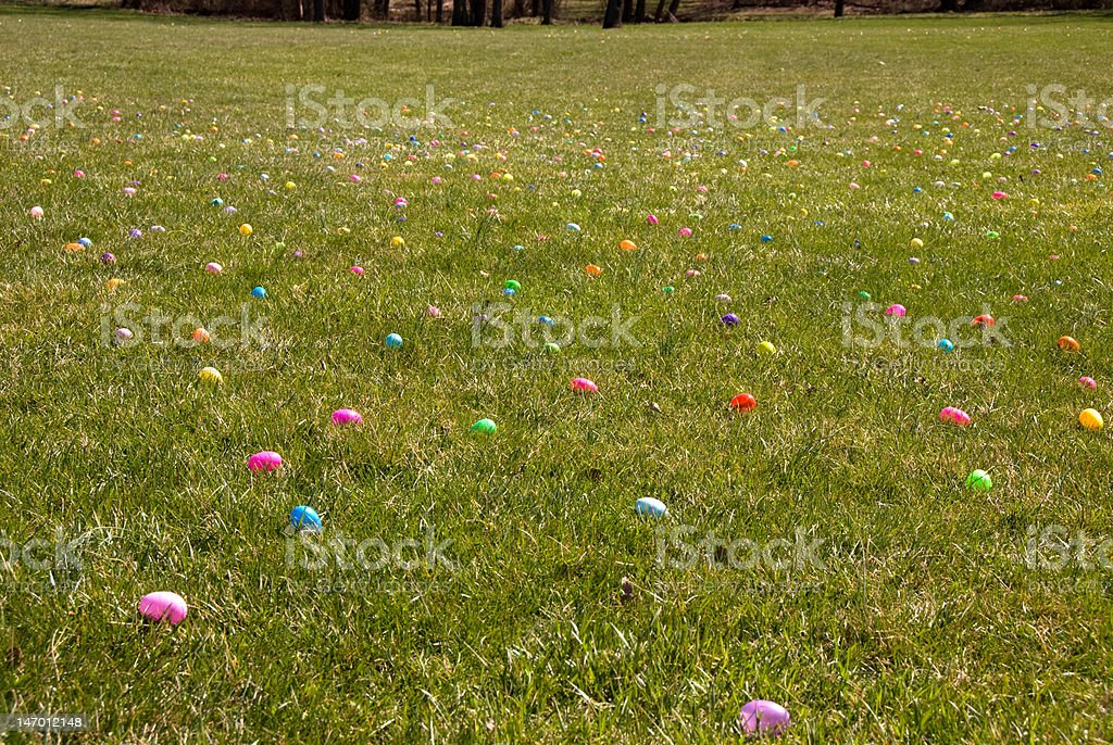 Grassy field strewn with colorful easter eggs royalty-free stock photo