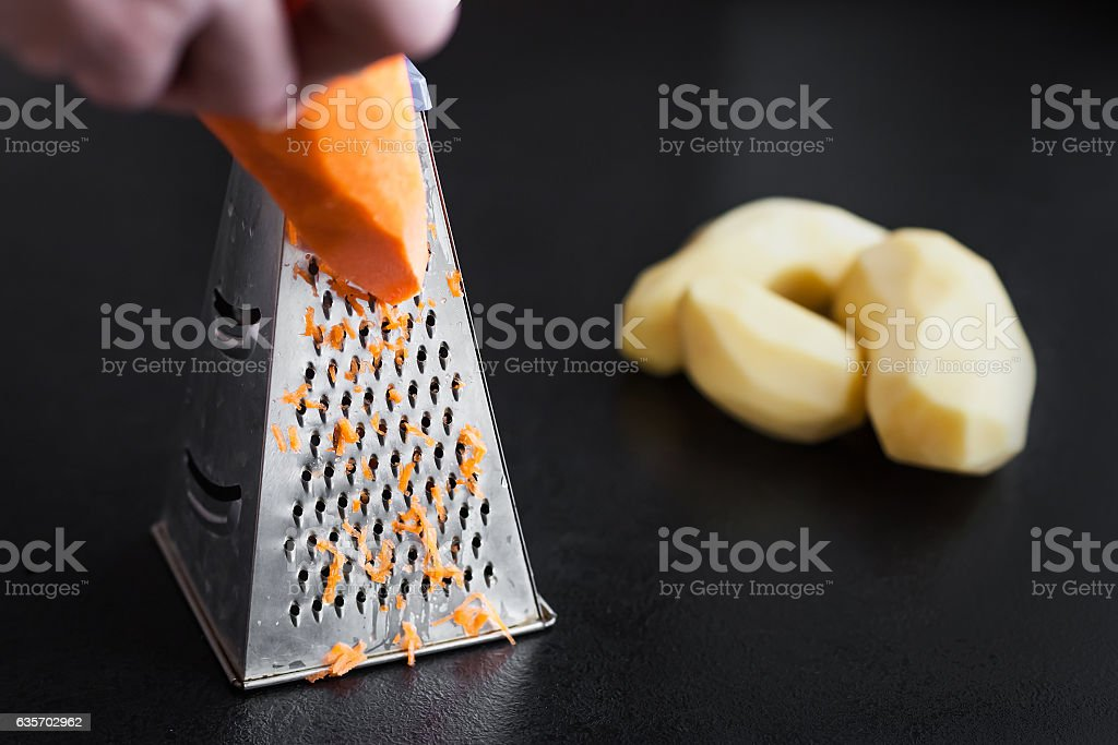grate carrots on a grater royalty-free stock photo