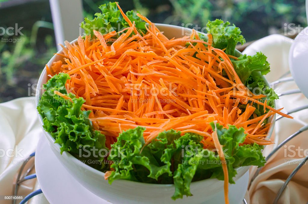 Grated carrots in a glass cup stock photo