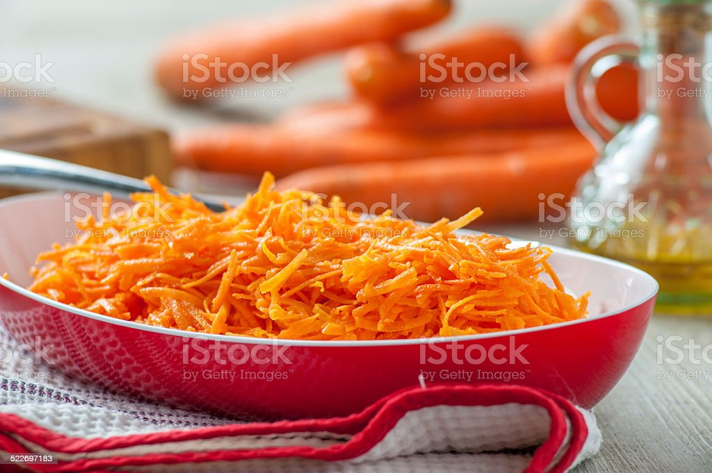 grated carrots in a white bowl stock photo