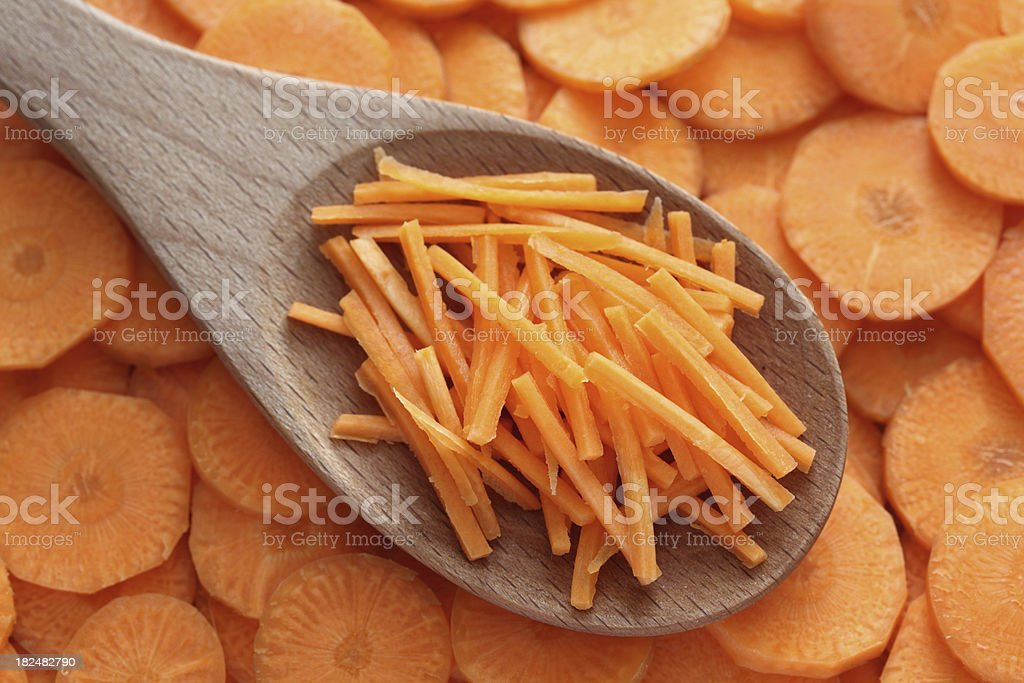 Grated carrots in a wooden spoon royalty-free stock photo