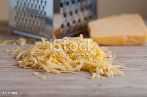 Grated cheddar cheese on wooden board with cheese grater and a block of cheese in the backgroound.  Focus is on the grated cheese.  Selective FocusTo see more of my food images click on the link below:
