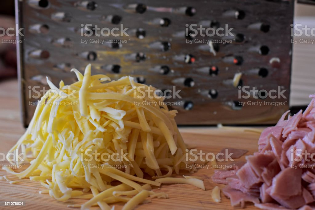 Grated cheese, chopped ham, balls of mozzarella and grater on wooden background stock photo