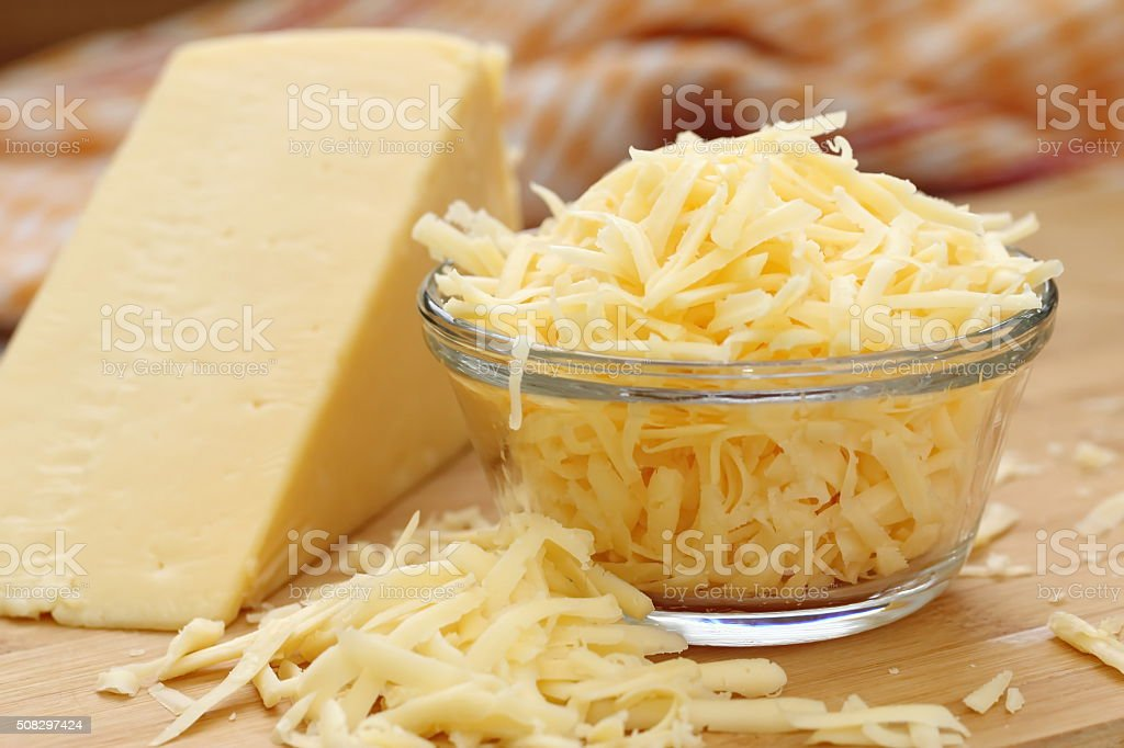 Grated cheese in a glass bowl stock photo
