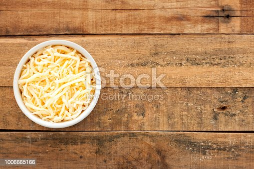 Top view of white bowl full of grated cheese over wooden table