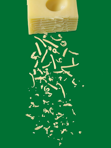Cheese sprinkles on green background with clipping path