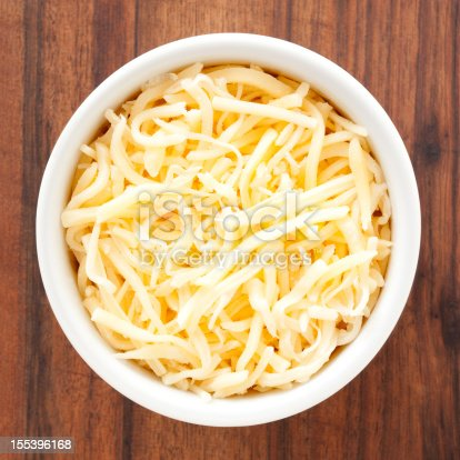 Top view of white bowl full of grated cheese