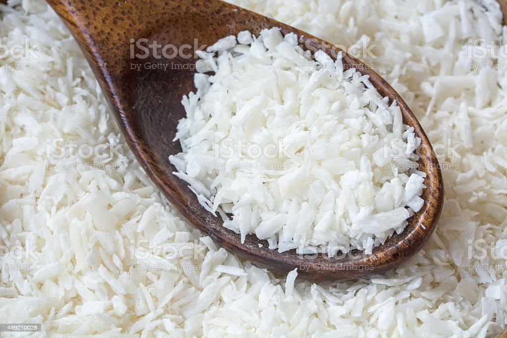 Grated coconut flakes with a wooden spoon stock photo