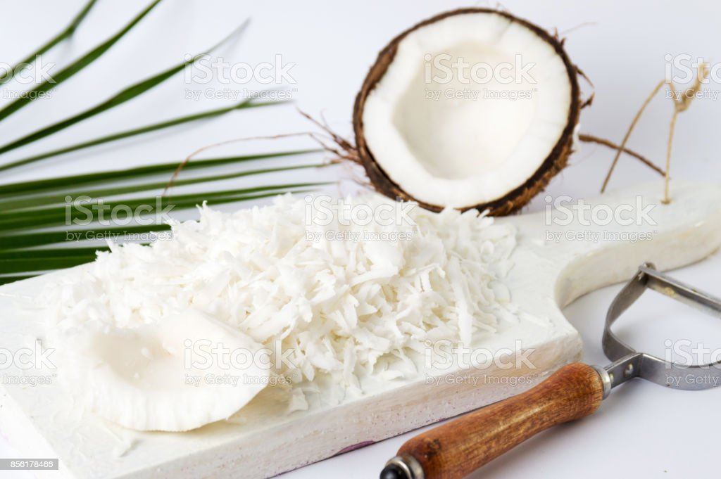 Grated coconut on a wooden board stock photo