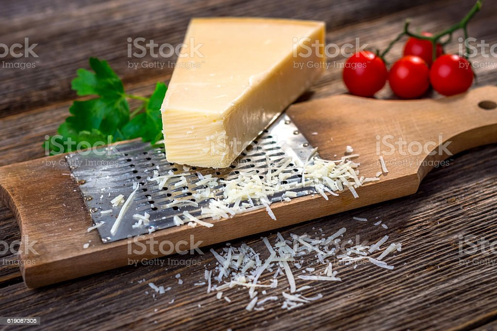 Grated parmesan cheese and  grater on wooden background stock photo