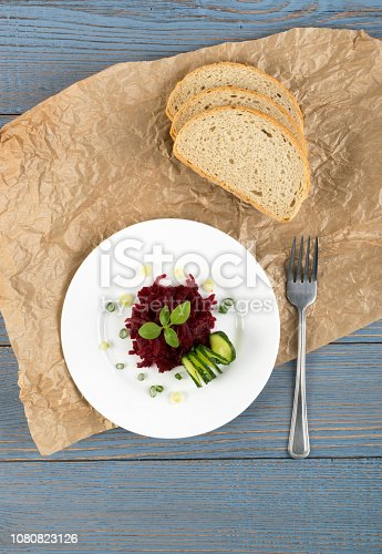 Exquisite Serving Restaurant Plate of Grated Pickled Beet Root Salad on Rustic Background Top View. Macro Photo of Homemade Marinated Beetroot in Sour and Sweet Souse with Green Onions and Cucumber