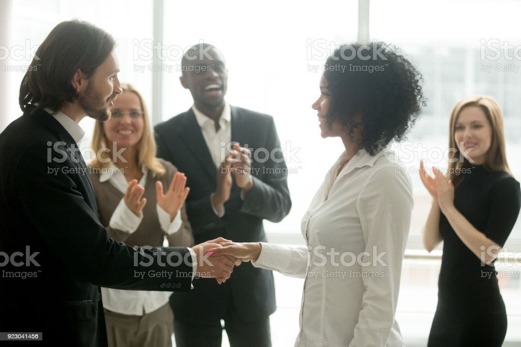 Grateful boss handshaking promoting african businesswoman congratulating with career achievement royalty-free stock photo