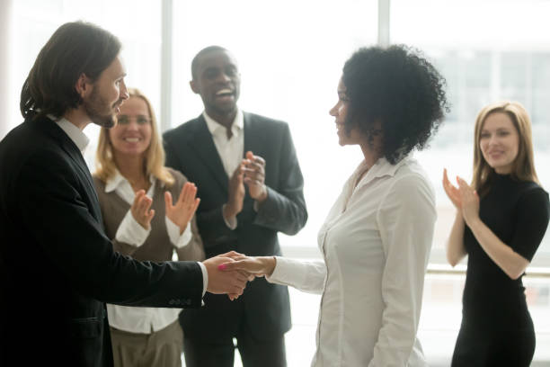 Grateful boss handshaking promoting african businesswoman congratulating with career achievement stock photo